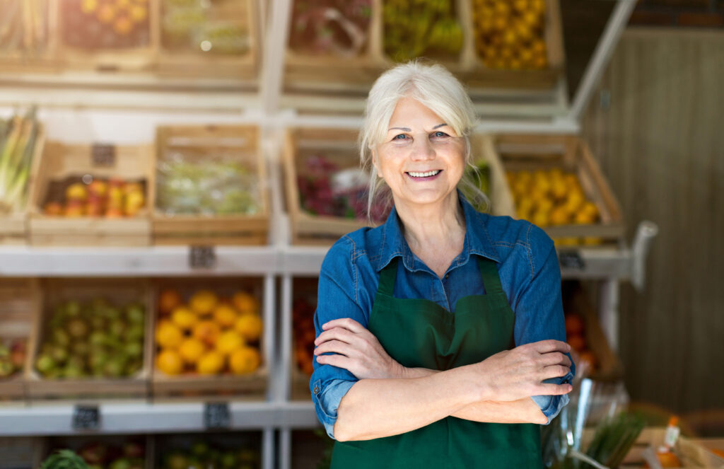 portrait-of-confident-owner-with-arms-crossed-standing-in-small-grocery-store